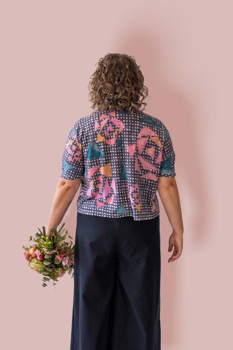 Back view of woman wearing Asmuss Limited Edition Boxy Cropped T-shirt with the Painterly Rose Print holding a gorgeous bunch of flowers. The print has a black and white check background with a geometric interpretation of the Evelyn rose. It is a blend of wool and innovative temperature regulating 37.5 Technology helps keep you feeling dry and comfortable all day long. It is a perfect elevated t-shirt with clever detailing to add to its style.