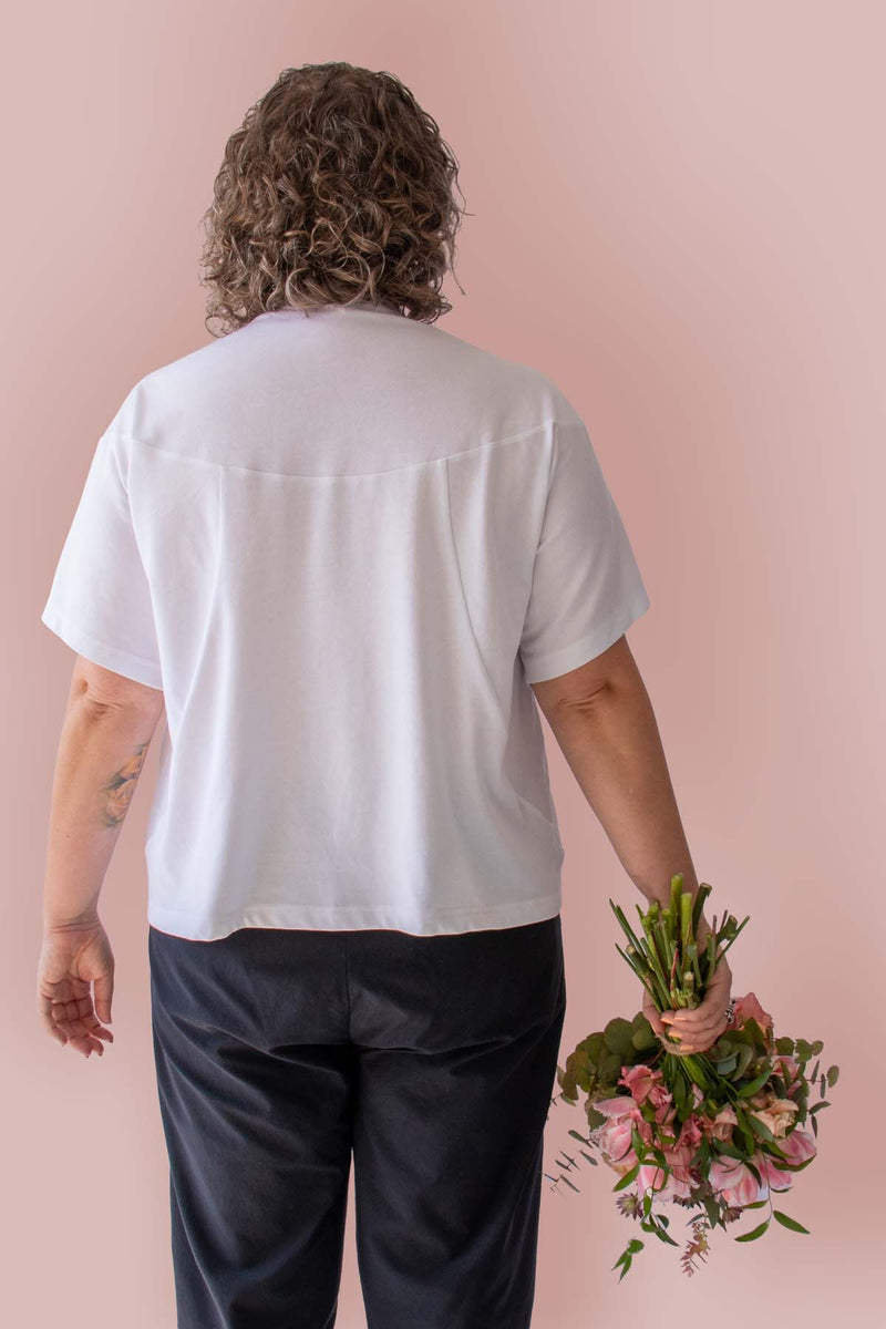 Back view of Asmuss Panelled T-shirt in White Organic Cotton and Recycled Polyester worn by Clare with a beautiful bunch of flowers.