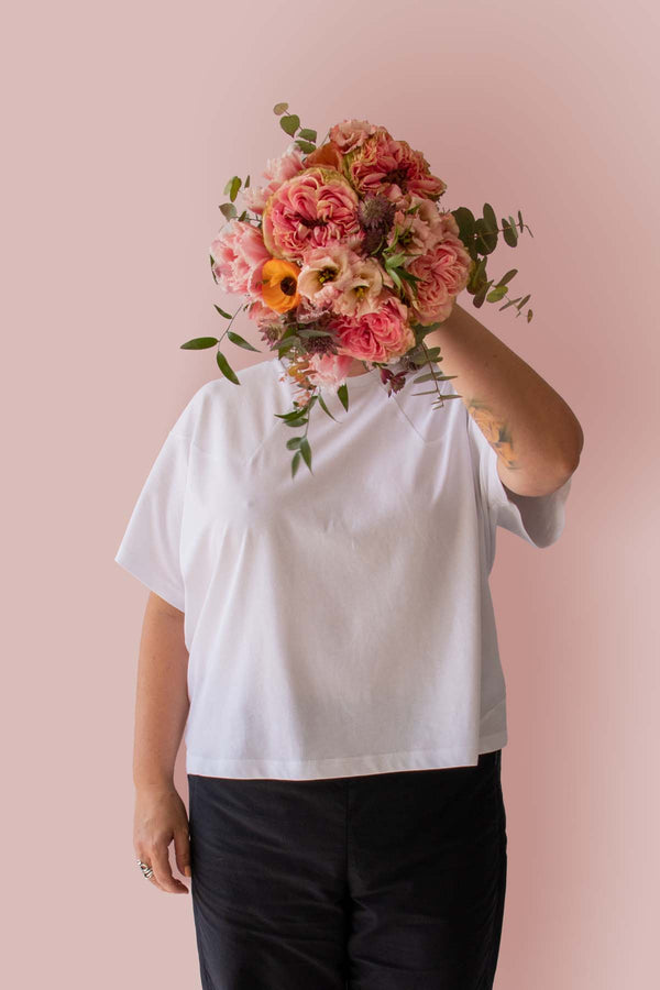 Asmuss Panelled T-shirt in White Organic Cotton and Recycled Polyester worn by Clare with a beautiful bunch of flowers in front of her face.