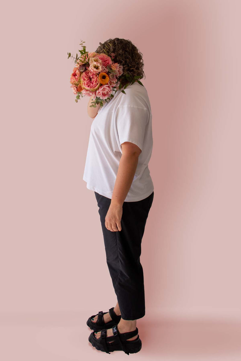 Side view of Asmuss Panelled T-shirt in White Organic Cotton and Recycled Polyester worn by Clare with a beautiful bunch of flowers in front of her face.