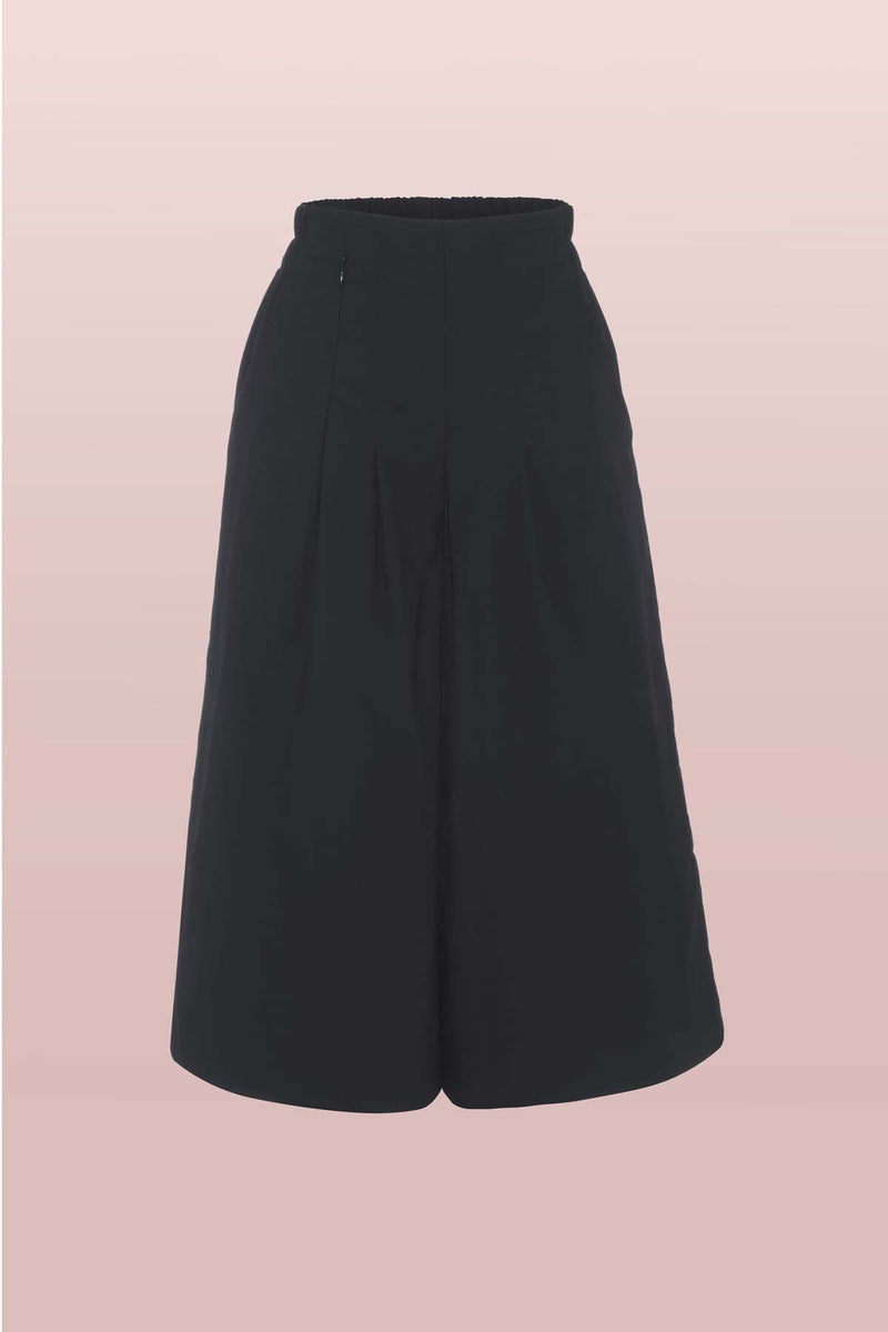 Front view of the Asmuss Pleated Culottes in Black featuring elasticated waste for comfort and a hidden zipped pocket in the front pleats as well as side pockets. The cropped wide leg culottes are perfect elevated essentials for everyday. Great sustainable culottes for the outdoors, travel or everyday adventures with stretch and water resistance in a sustainable fabric..