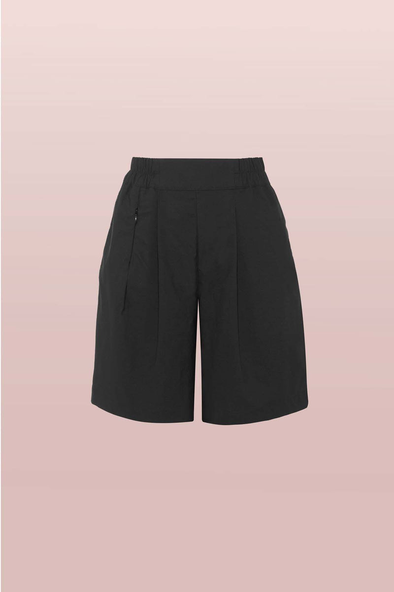 Front view of the Asmuss Pleated Shorts in Black. Made from a sustainable castor bean based fabric that has built in stretch and water resistance they feature side pockets and a hidden zip pocket in the pleats. Stylish, sustainable lifestyle womenswear for your everyday and travel adventures. An essential elevated beyond activewear.