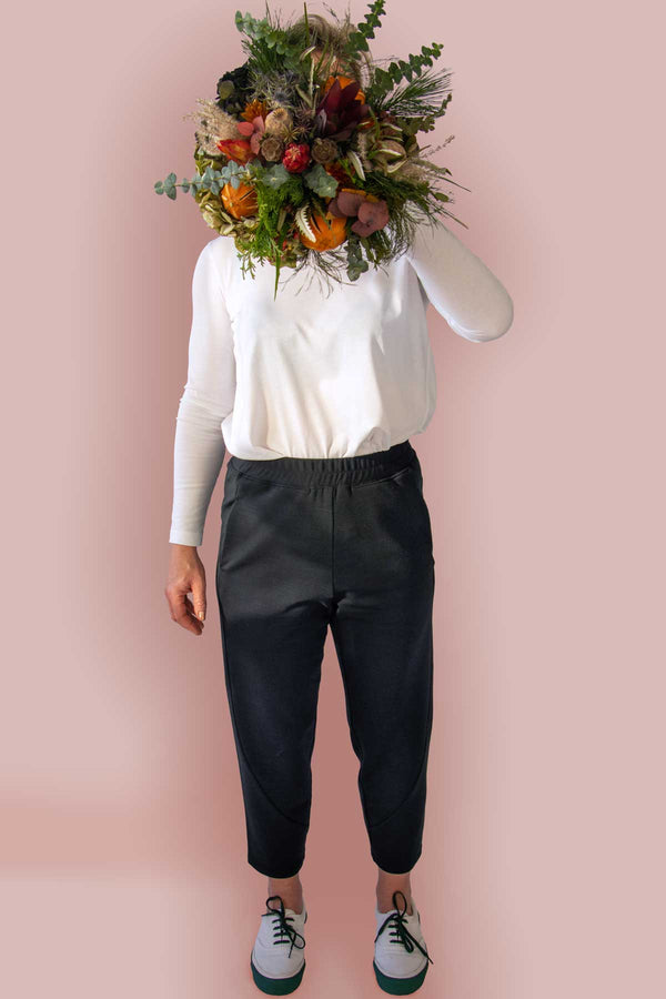 The Asmuss Beyond Track Pants or Joggers in Black Wool Fleece worn by a friend as model with a dried flower arrangement in front of her face