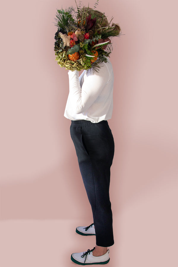 Side view of the Asmuss Beyond Track Pants or Joggers in Black Wool Fleece worn by a friend as model with a dried flower arrangement in front of her face