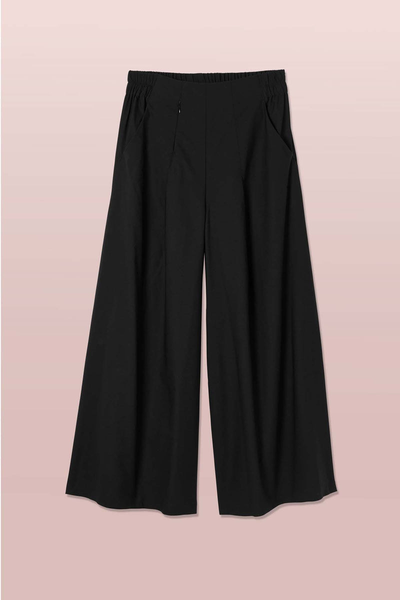 Front view of the Asmuss Wide Leg Trouser in black. Made in the UK in small batches from a sustainable fabric with built in stretch and water resistance. Stylish, sustainable trousers that are elevated by the design details including hidden zip pocket and high elasticated waist for convenience and comfort. Perfect for all your everyday or travel adventures.