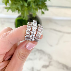 Alexandra Marks holding an oval eternity band, a cushion cut eternity band and the baguette eternity band in silver