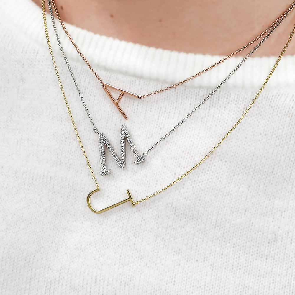 Layering Alexandra Marks sideways initial necklaces in gold, silver and rose gold