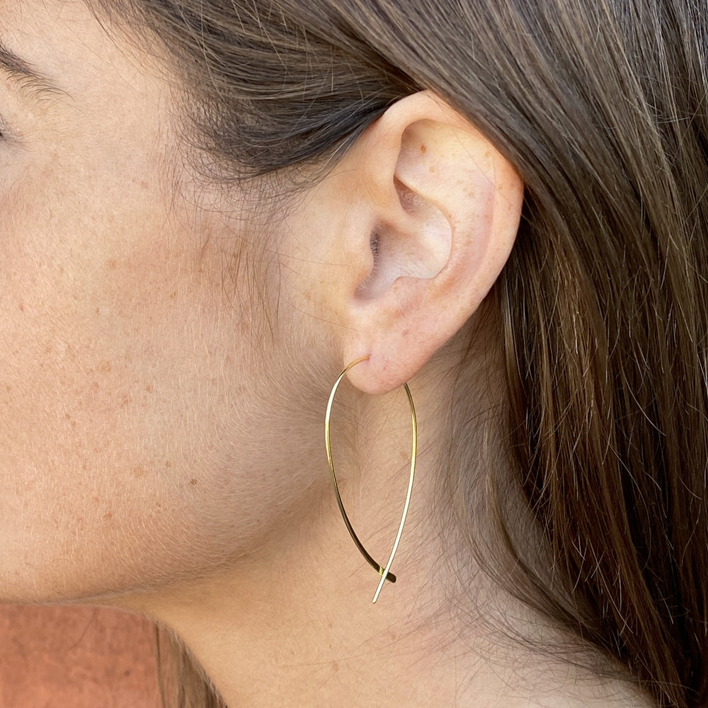 Model wearing the thin gold criss cross hoop earrings