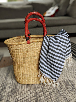 Natural woven beach bag with leather covered handle paired with a black and white large Turkish beach towel