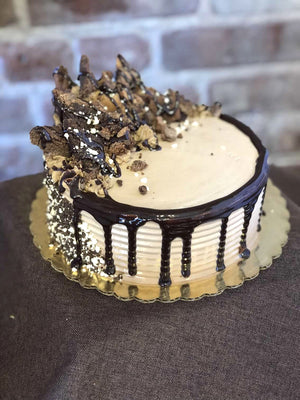 The brownie lover's cake has a mountainous cluster of brownie chunks placed on top of chocolate whipped cream. Flowing from brownie mountain is a waterfall of chocolate fudge and an avalanche of chocolate and vanilla cake crunch which forms a crown around the base of the cake.