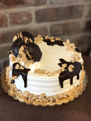 This cake is supreme when it comes to cookie dough. We generously parcel our dough pieces around the top and bottom of our cake while fudge cascades down the edges. We also include chocolate chip cookies dipped in chocolate to make a delectable display on top of the cake.