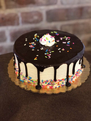 This ice cream cake will be the highlight of any birthday party as it combines enthusiasm with simplicity. Vanilla whipped cream is dressed in a glaze of chocolate fudge and brought to life with a colorful display of rainbow sprinkles around the base of the cake.