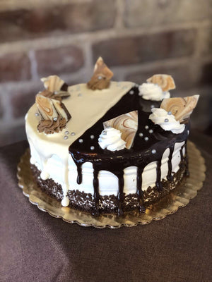 This cake is covered half by a marshmallow drip and half by a chocolate glaze! Each side is also adorned with white and milk chocolate morsels atop dollops of vanilla and chocolate whipped cream while decorated with edible nonpareils.