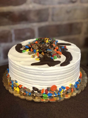 Everyone's classic candy in ice cream cake form! This quintessential classic is covered in vanilla whipped cream and accompanied by a ring of M&Ms around the base of the cake. On the top of this dessert you'll find a pool of M&Ms swimming in a hard chocolate shell and chocolate whipped cream.