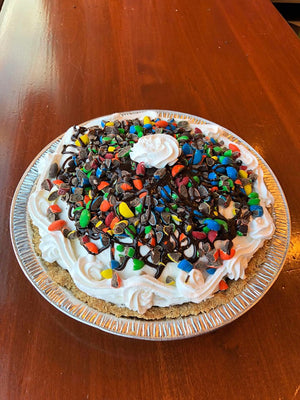 Here you'll find Chocolate Chip Cookie Dough ice cream accompanied by a colorful garnish of M&Ms and fudge! At the bottom of your slice is our homemade graham crust and vanilla whipped cream for a softer sweetness to accompany the hard M&M pieces.