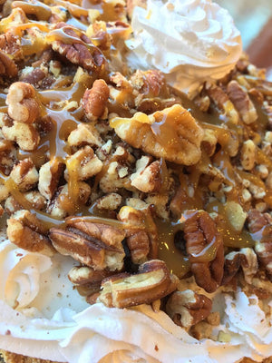 Sitting in our homemade graham pie crust is a wonderful portion of Butter Pecan ice cream decked out in caramel, salted pecans and vanilla whipped cream.