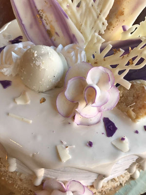 Unlocked from the Torico vault and here to intrigue you is a delicacy made of majestic lavender white chocolate and glimmering golden embers. This devilishly delicious dessert is cloaked in a marshmallow drip and topped with hand rolled pound cake truffles that have been dipped in white chocolate. You don't want to miss the opportunity to satisfy your taste buds with this ice cream cake.