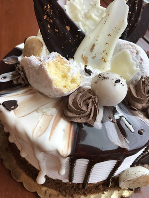 Elegantly draped in chocolate fudge and marshmallow toppings, all desserts will pale in comparison. This dessert is adorned in white and dark chocolates and accented with hand rolled pound cake truffles and donuts. This cake will easily be the talk of the party once you indulge in something this chic.
