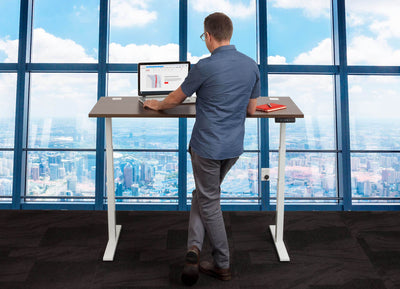 Man Standing at Standing Desk in Front of City Scape