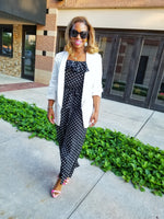 Black and white polka dot jumpsuit with off the shoulders crossed tie sleeves. Ruffled top. Adjustable ties on the sleeves. Elastic waistband with tie closure belt. Easy to wear to the office with a blazer then transition to a flirty look after work. Lined pants.