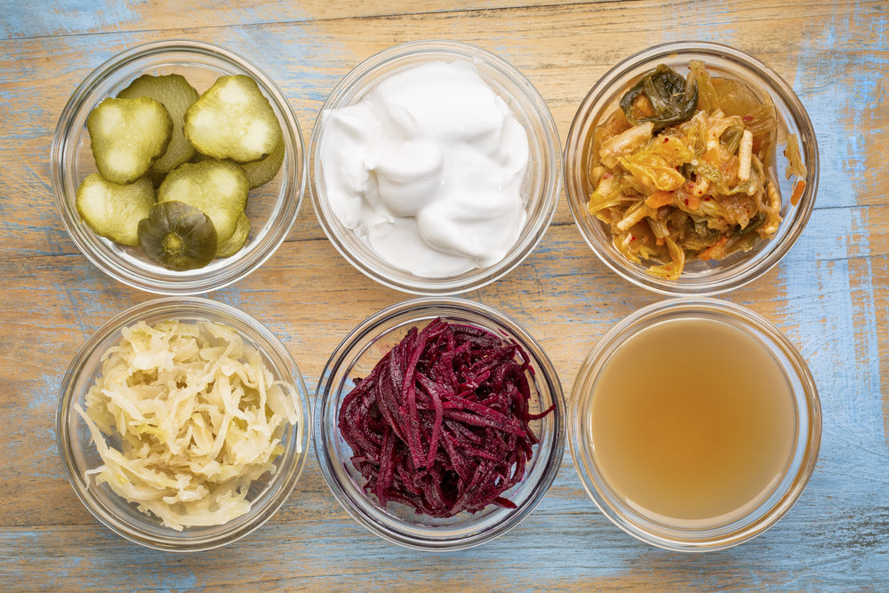 Six glass bowls of fermented foods, including pickles, yogurt, kimchi and beets