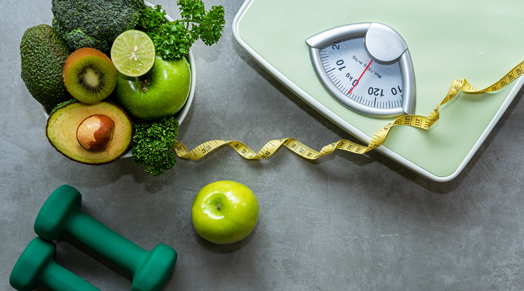 A scale, hand weights and a bowl of healthy foods