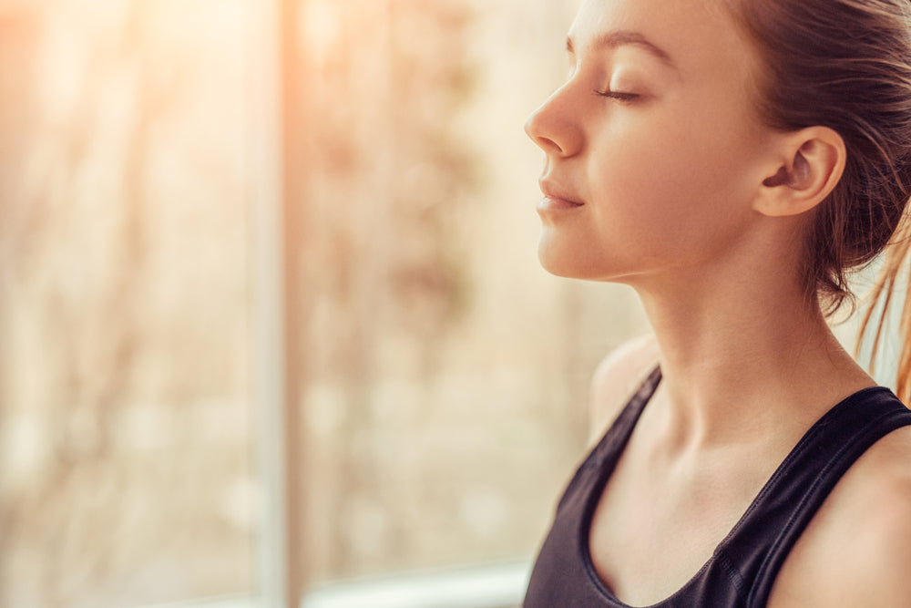 Side view of young female with closed eyes breathing deeply while doing respiration exercise during yoga session in gym