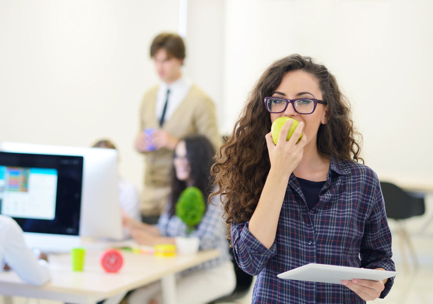 Portrait of pretty young woman eating an apple in her office.