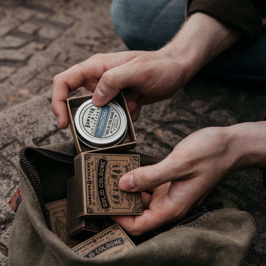 A man putting Aroostook solid cologne into a travel bag