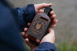 a man holding Wahya beard wash in the outdoors by Bawston & Tucker