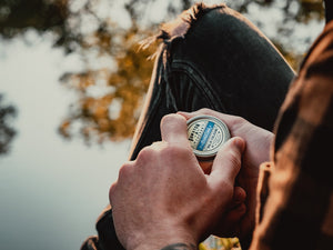 Guy opening Aroostook solid cologne tin