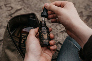 A man with beard oil and travel bag apply beard oil by Bawston & Tucker
