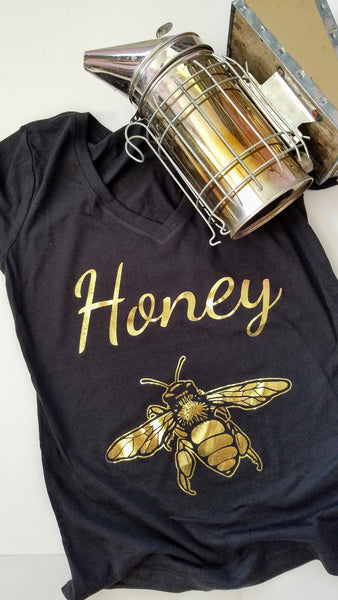 Gold Honey Bee Women's T-shirt. Make a statement and look your best in this fabulous gold foil tee. Soft cotton makes this shirt easy to wear. The bright crisp gold design is the perfect addition to your sunny spring wardrobe.   Limited edition. Wash gentle inside out and hang dry.  Cotton/poly blend, laundered, tearaway label, form fitted. Can size up.