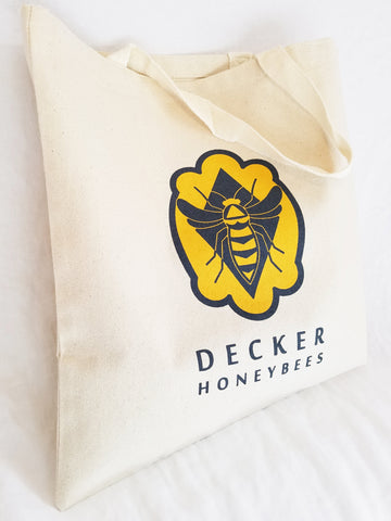 "Decker Honeybees Logo Tote. This reusable canvas tote bag is a must have for your everyday life. Use it for groceries, the gym, class or your next festival.   12.0 oz., 100% heavy canvas 20"" web canvas handles, 9"" drop 15""W x 16""H   Hand wash only/Printed on one side.  Easy on the environment!"