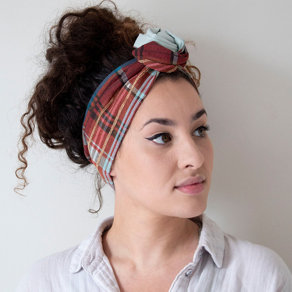 woman wearing a silk fabric headband in a checkprint with a fron flower knot