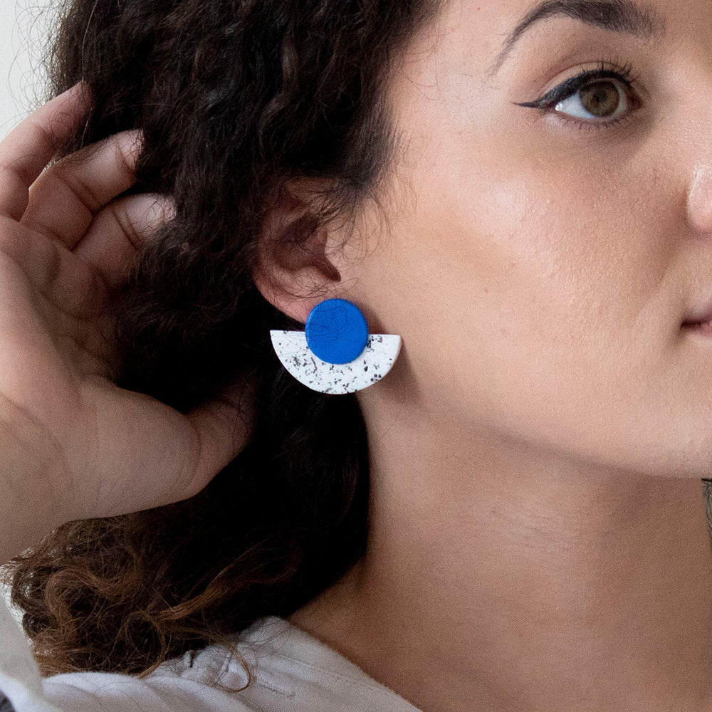 woman wearing the Maya stud earring in a cobalt blue colour circle on white & black semi circle