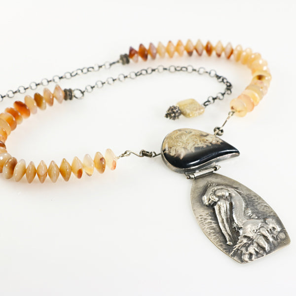 Silver repousse pelican necklace with petrified palm root - jbEbert studio art jewelry