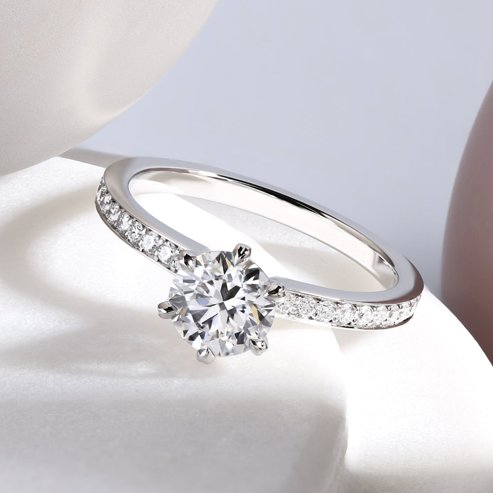 Classic round diamond engagement ring with a diamond set band, in platinum
