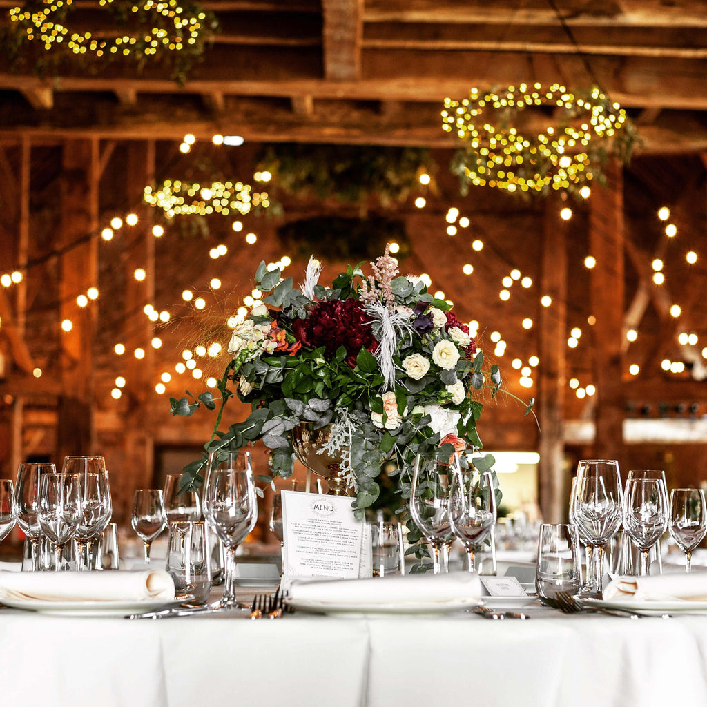 Barn wedding table setting with flower centre piece and fairy lights