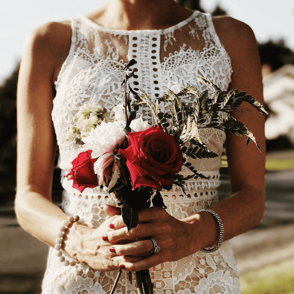 Bride holding red flower bouquet and showing her diamond engagement ring and wedding ring