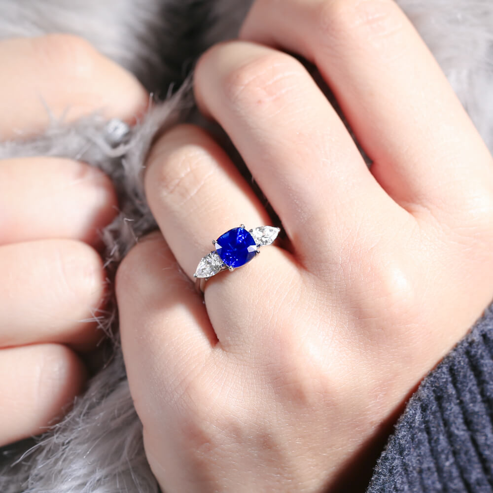 Trilogy style engagement ring with a bright blue sapphire and two pear diamonds