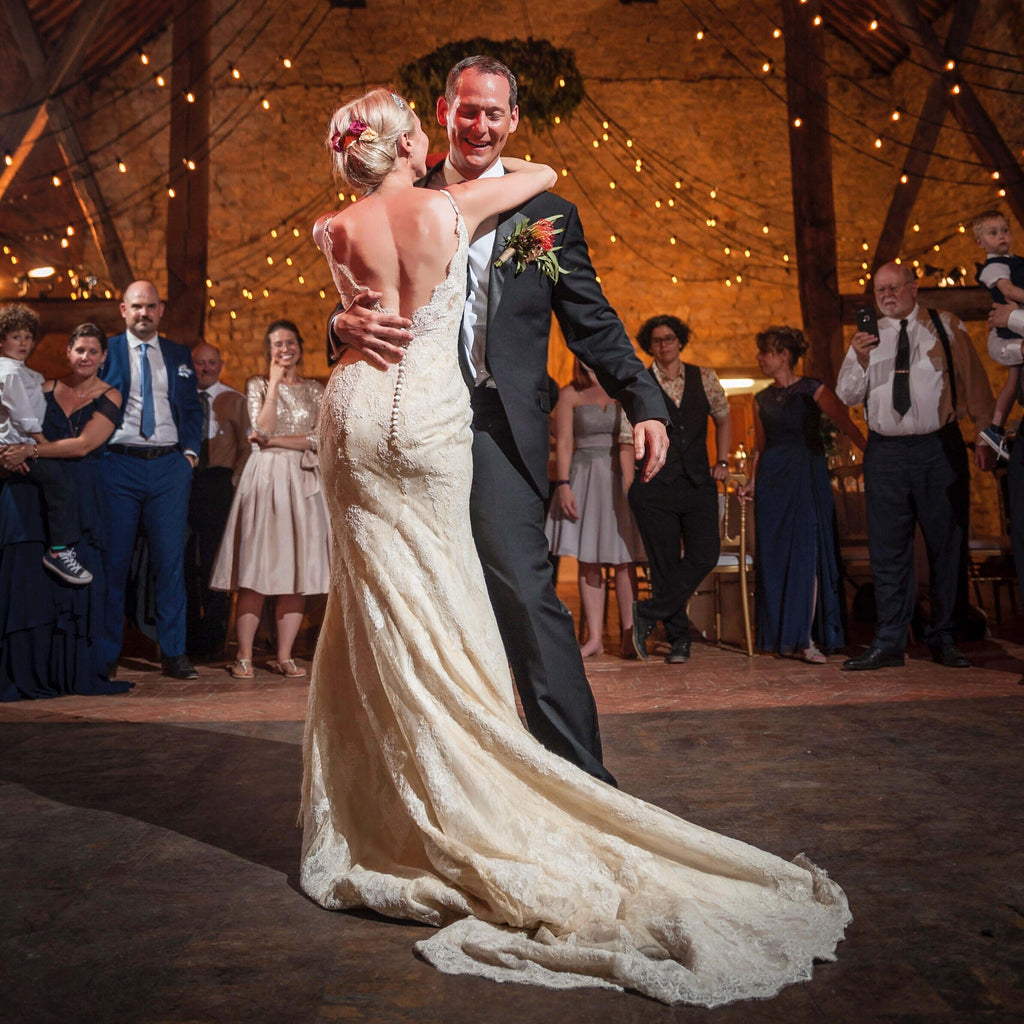 Bride and Groom's first dance in barn with fairy lights, bride wearing vintage Art Deco wedding dress