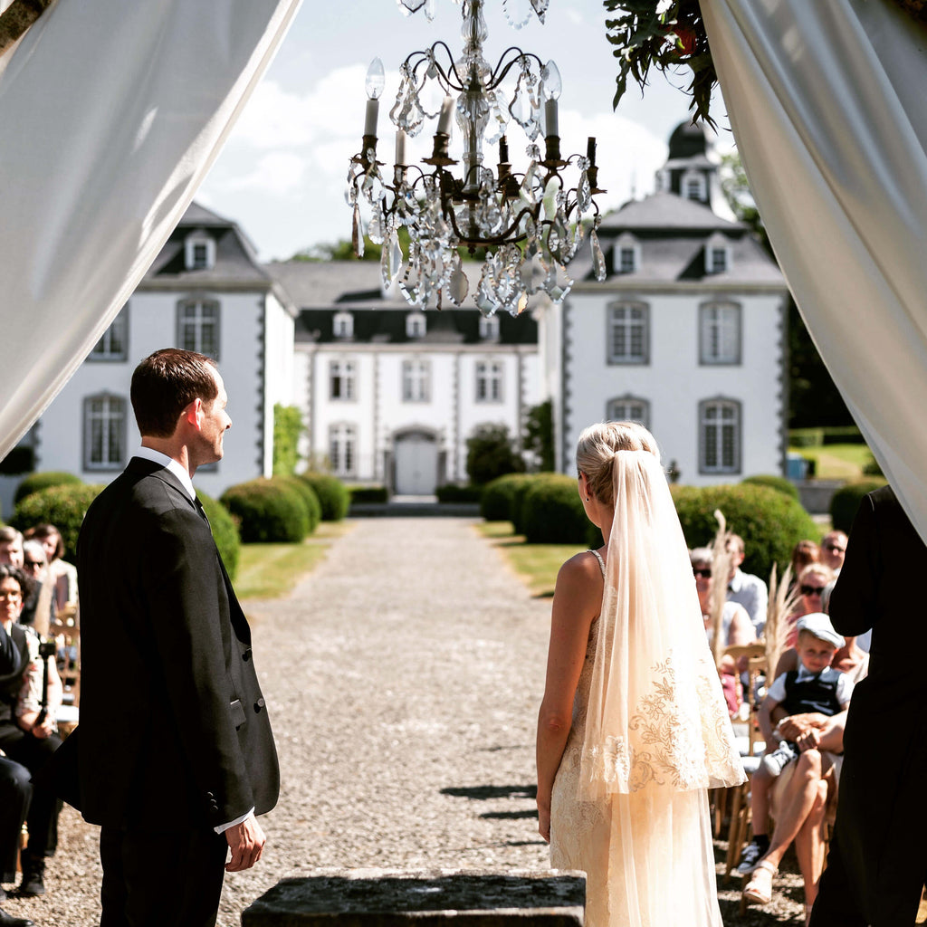 Bride and Groom at the altar, in front of a chateau with a chandelier overhead