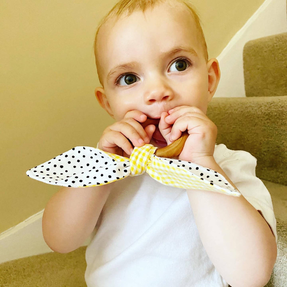 toddler chewing on wooden teething ring tied with fabric bunny ears