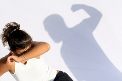 women cowering on a white background with a shadow of a man shouting abuse