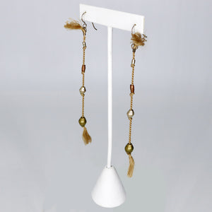 By Brandi Kruse Materials: African Brass and Beige Silk Measures: 4 3/4 inches long.