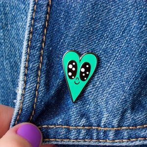 By Chris Uphues. This Minty Heart Pin is made with super shiny black nickel and filled with smooth, high quality, enamel in seafoam and white. Pin comes with a rubber clutch for extra grip and mounted on Chris Uphues packaging. Perfect for gifting! Pin measures 1 inch tall. Also available in store at FOLD Gallery DTLA.