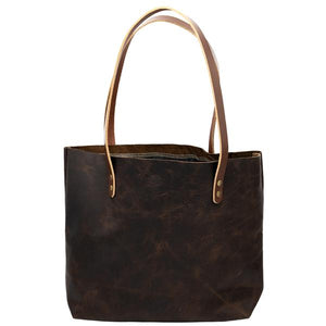 By Hawks & Doves. Rustic Tote Short in Chocolate. This tote is constructed with full grain oil tanned leather. The leather is treated with oils and waxes which keep it conditioned for a long time and allows the bag to wear in and age wonderfully. Has an interior hang pocket. Shoulder straps have about a 10 inch drop (approximately 23 inch strap). Measures 14 inch wide x 11 inch high x 3 inch deep. Also available in store at FOLD Gallery DTLA.