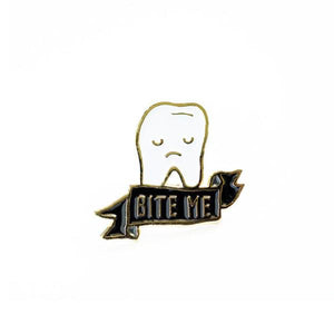 By Ilootpaperie. Soft enamel Bite Me Tooth Pin with gold base. Ships as a single pin on card. Measures 1 inch.