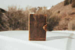 By Kodiak Leather. The Drifter Leather Journal in Antique Brown is the perfect travel companion. Made from Full Grain leather and complete with a snap button closure, this journal is the ultimate gift item for the world traveler or home body. 210 blank pages. Handmade artisan paper. Refillable. 5 x 7 x 2.5 inches.